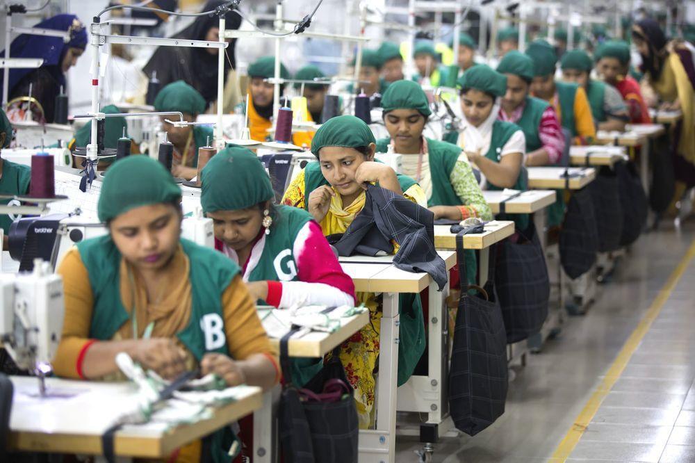 孟加拉一處成衣工廠內的作業員努力縫製衣料。(美聯社)