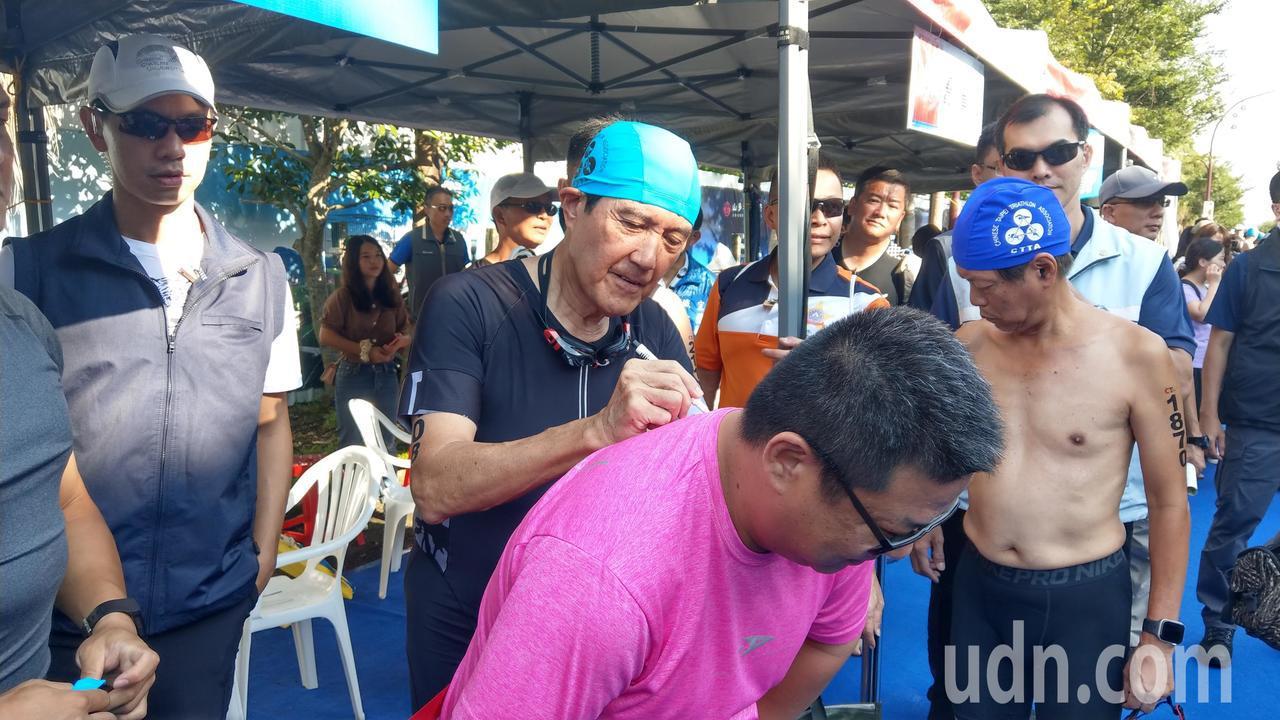 馬英九到宜蘭梅花湖參加鐵人三項比賽,受到民眾熱情歡迎,要求在運動衫簽名。記者戴永...