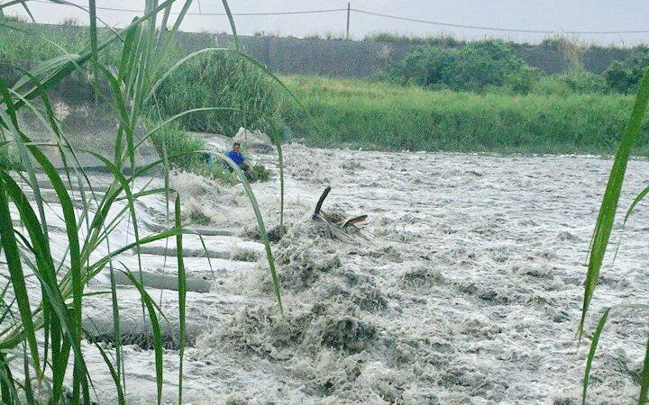儘管天氣晴朗但溪水暴漲,釣客來不及逃,登上消波塊上待援。圖/消防隊提供