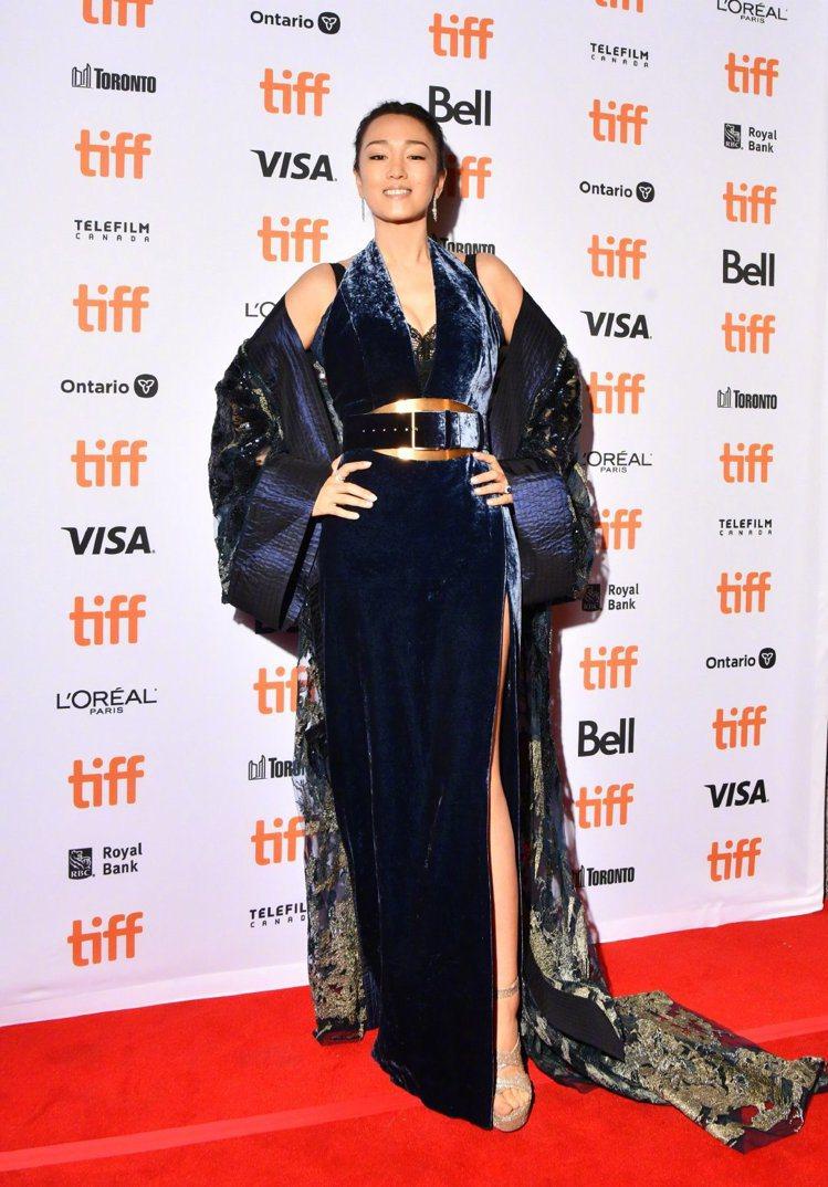 鞏俐挑選藍色高衩絲絨裙加上金色腰封,並搭配帶有蕾絲裝飾的和服式罩衫,並配戴Tif...