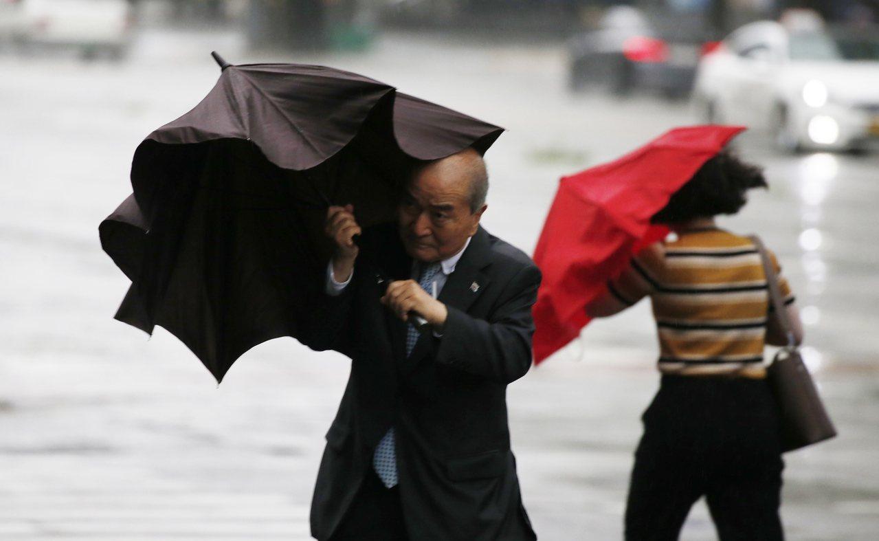 颱風玲玲侵襲南韓,首爾民眾的傘被強風吹到變形。(歐新社)