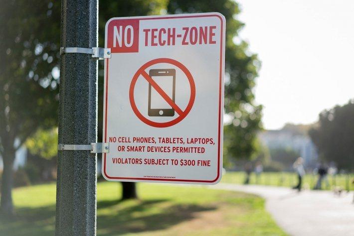 藝術家 Cash 在「此區無科技」標語上寫著:「禁用手機、平板、筆電或智慧型裝置...