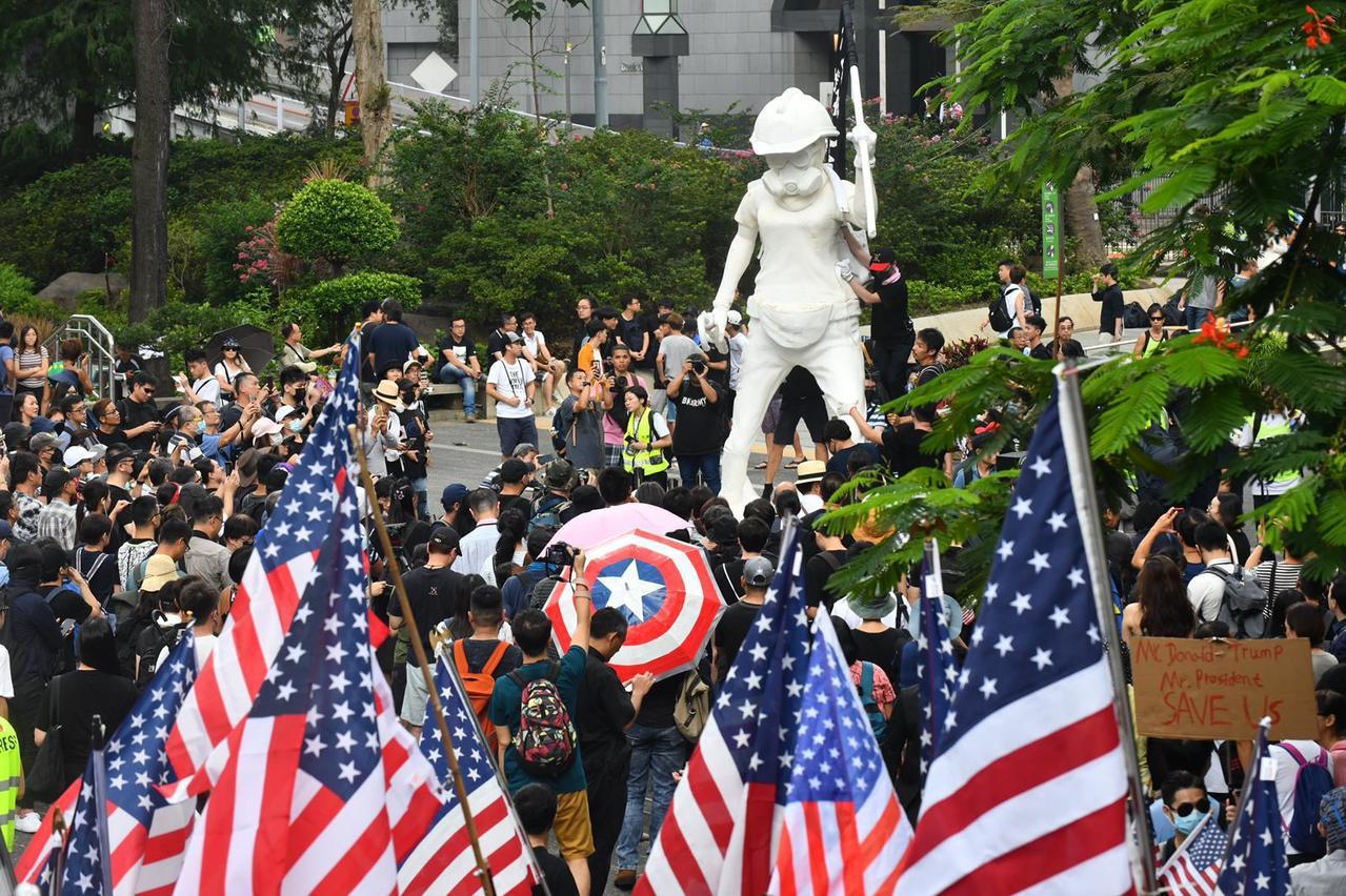 有香港市民8日攜美國旗參加遊行,目的引希望美國國會通過「香港人權與民主法案」。圖...