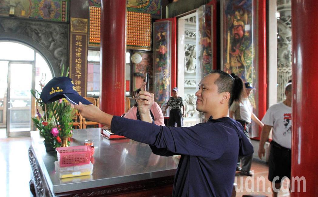民眾一大早就到埔鹽鄉順澤宮索取帽子,但因已經被搶光,只好跟廟方人員借來拍照打卡留...