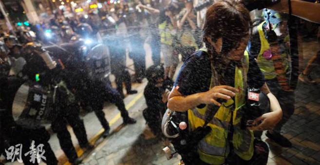 香港警員七日晚在聯合廣場外,向著只有記者的地方噴射胡椒噴劑。(明報網)