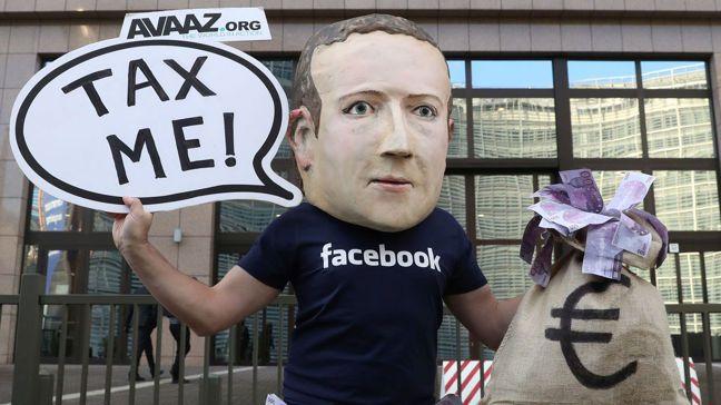 抗議人士在歐盟總部外裝扮成臉書創辦人,對跨國公司納稅很少的情形表達不滿。歐新社