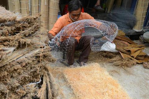一名印度工人正在編織草蓆,為製作「稻草冷氣」作準備。 圖/The Nationa...