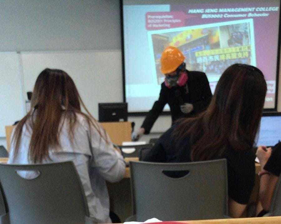 該名教師身穿黑衣,戴上頭盔和「豬嘴」口罩上課。圖:取自星島日報網站