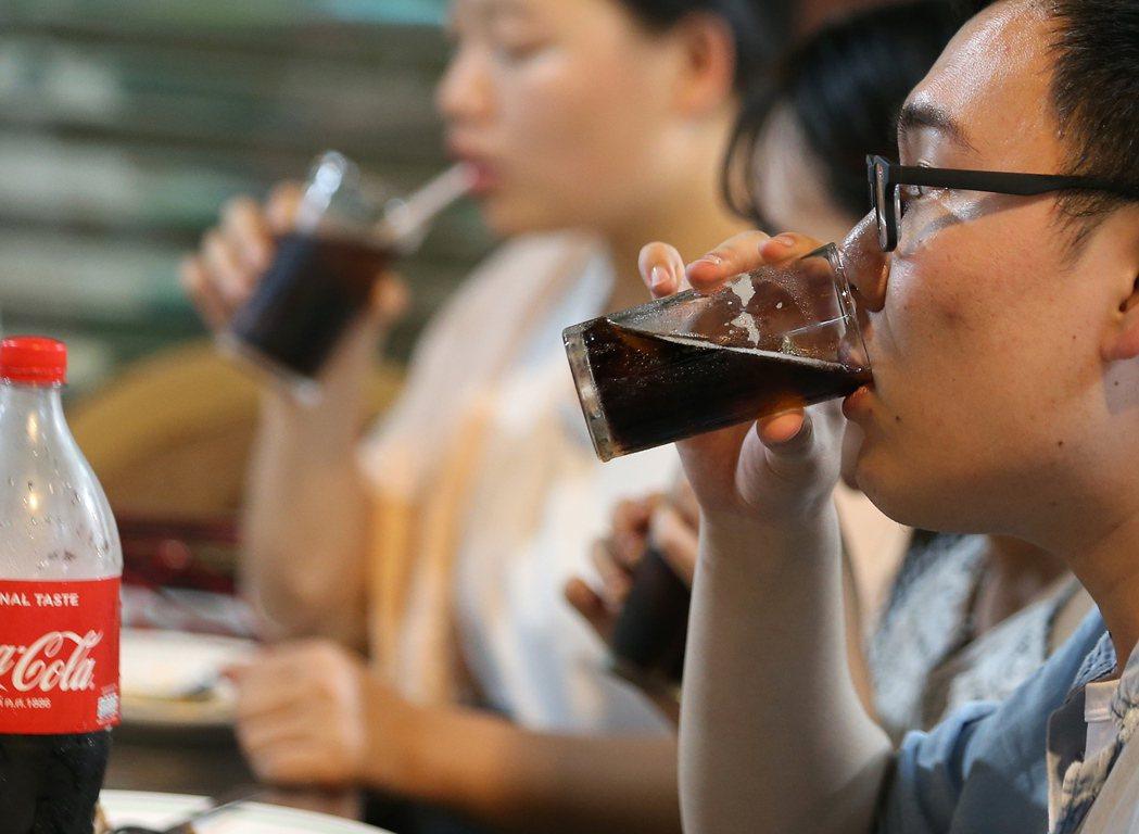 圖為泰國曼谷小吃攤客人正在喝含糖飲料。歐新社