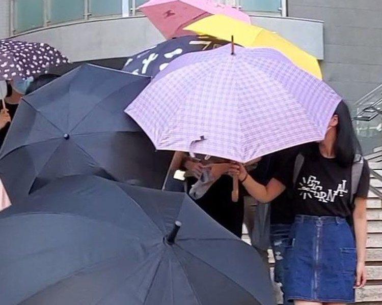 羅樂文(中黑衣女生旁)在多名親友掩護下離開法院。圖/取自星島日報網站