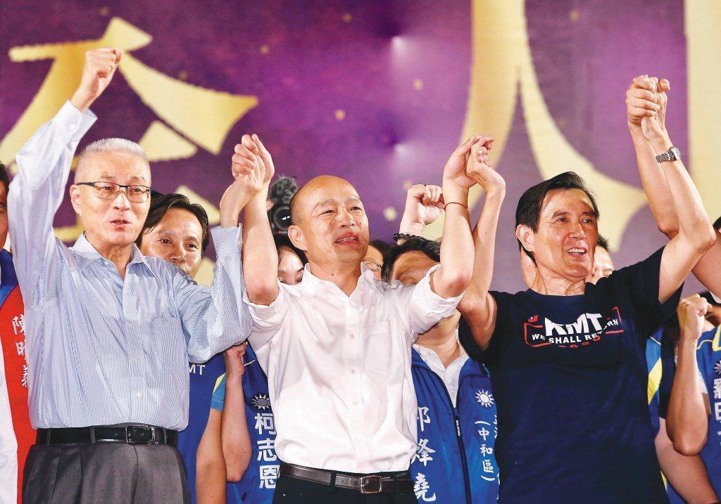 國民黨總統參選人韓國瑜(中)日前在三重水漾公園舉辦造勢晚會,黨主席吳敦義(左)與...