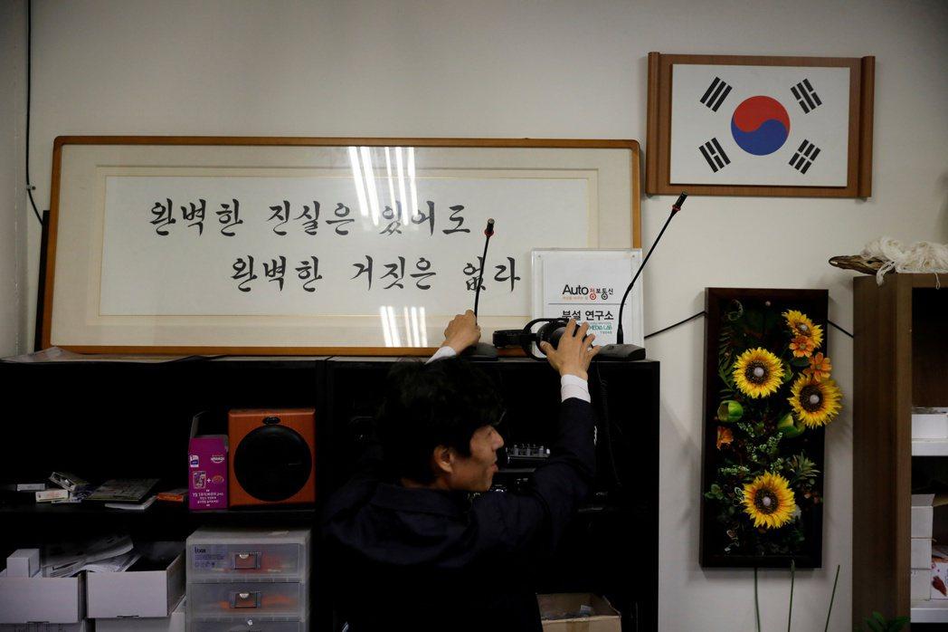販售密錄器的電子公司Auto Jungbo執行長張頌澈正在工作,上方是公司座右銘...