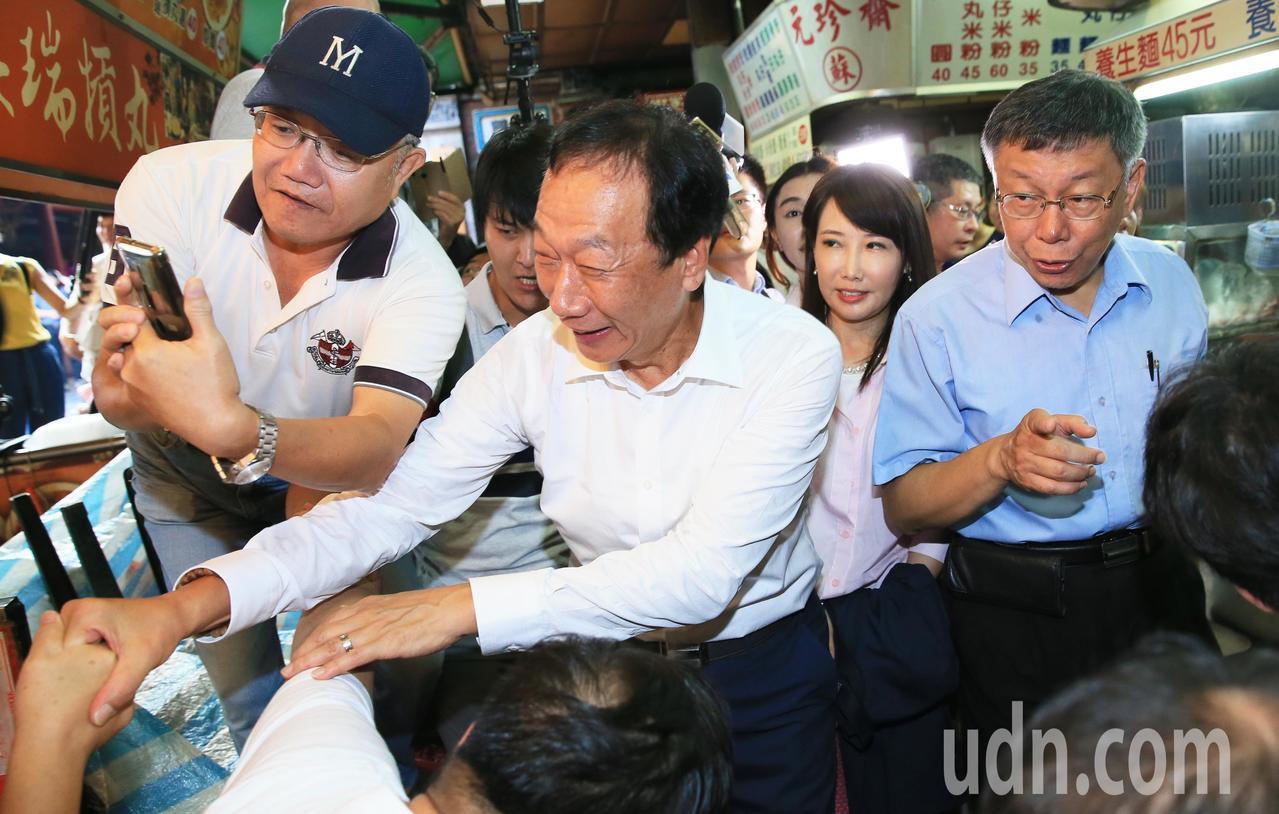 鴻海創辦人郭台銘(左二)與台北市長柯文哲(右)一早參拜新竹城隍廟,受到支持者的歡...