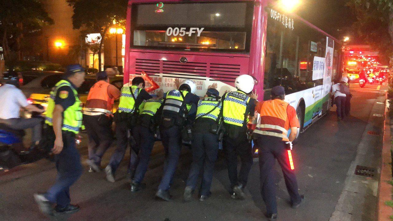 1輛公車在台北市基隆路拋錨,10名警察徒手推公車,熱心民眾上前幫忙,揮汗推車超過...