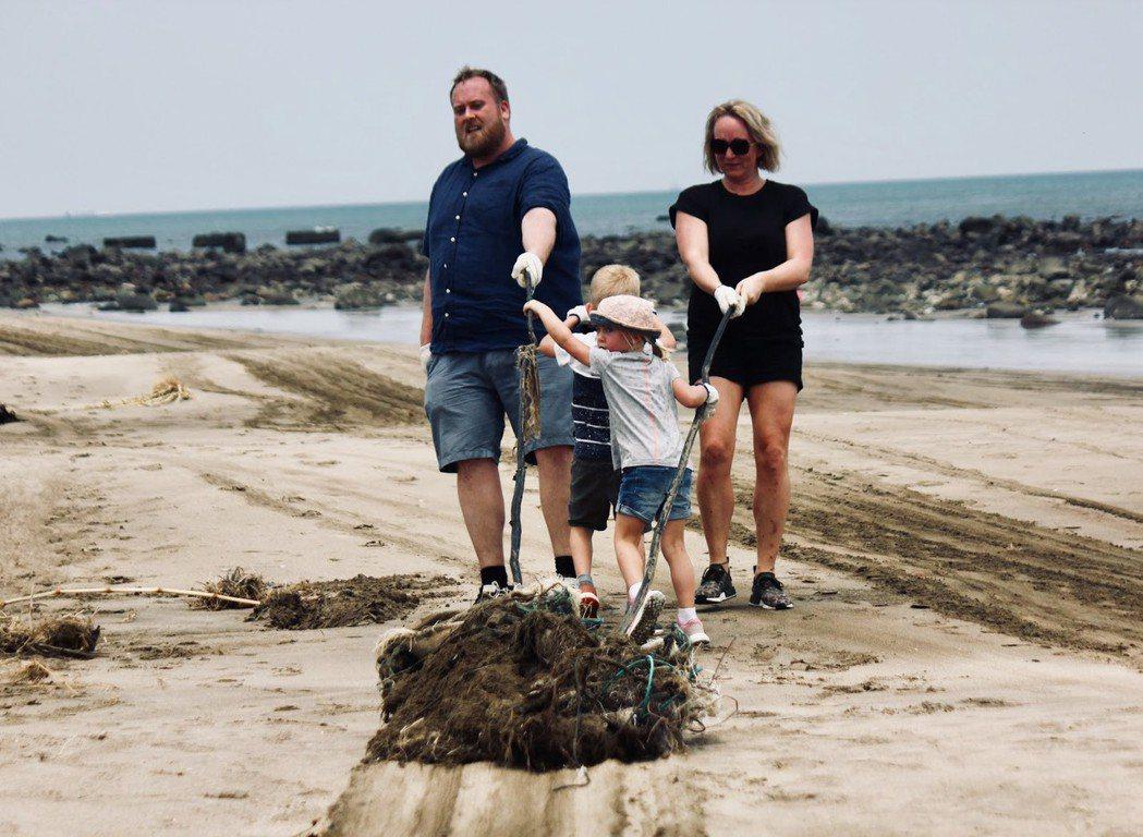 TAO全國淨灘日,一家人正拖行著難以搬動的打結漁網以及塑膠帆布。 圖/張璦攝影...