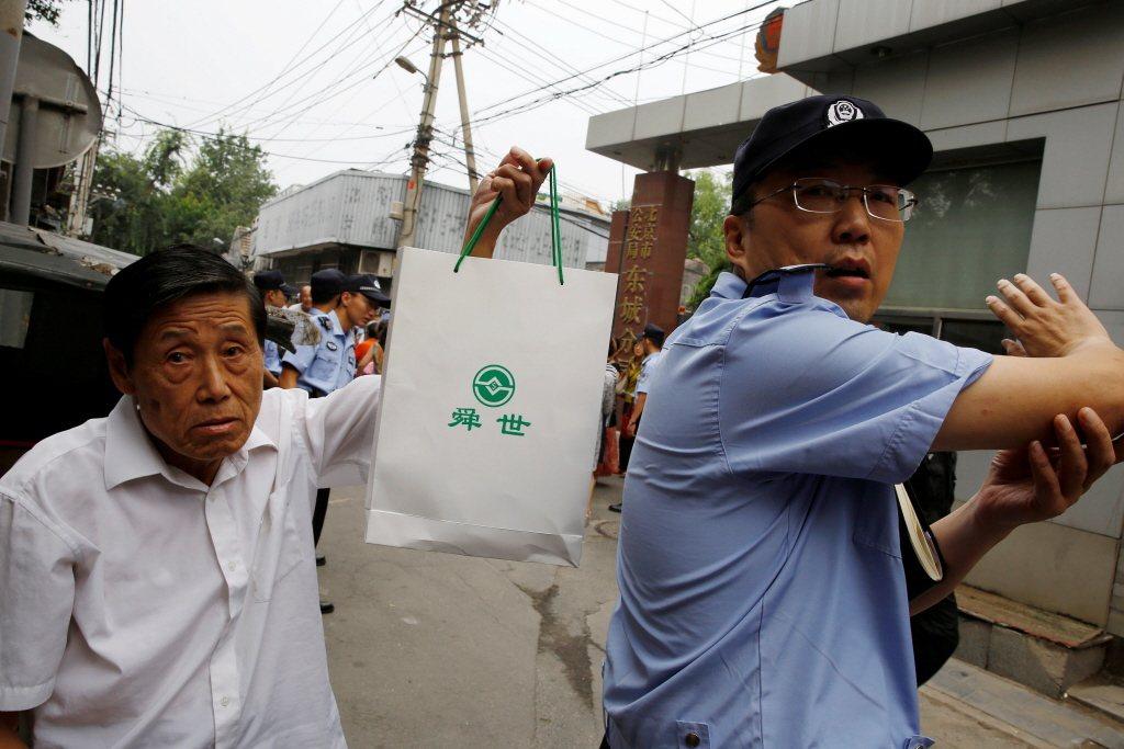 中國近期北京、上海、廣州、深圳等大城市連續發生P2P爆雷事件。圖為一名受害者上訪遭公安攔阻。 圖/路透社