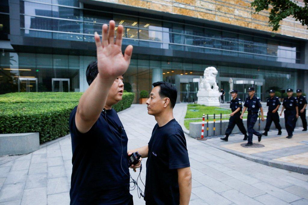 P2P受害者到北京金融街抗議,一名公安舉手阻擋記者拍攝。 圖/路透社