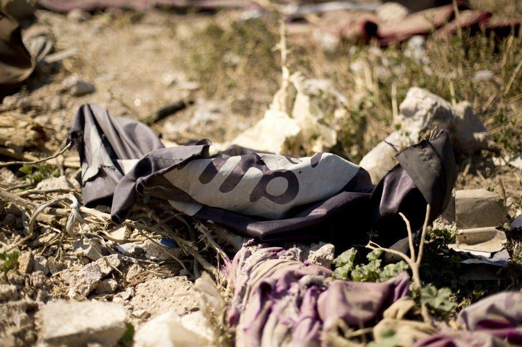 圖為敘利亞巴古茲村一面殘破的伊斯蘭國旗幟。 美聯社