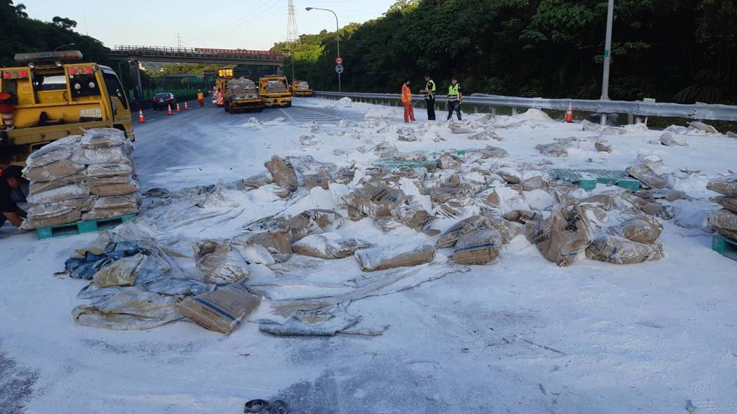 國道三號新台五入口匝道發生貨車翻覆意外,石灰灑落一地。圖/新北市交通局提供
