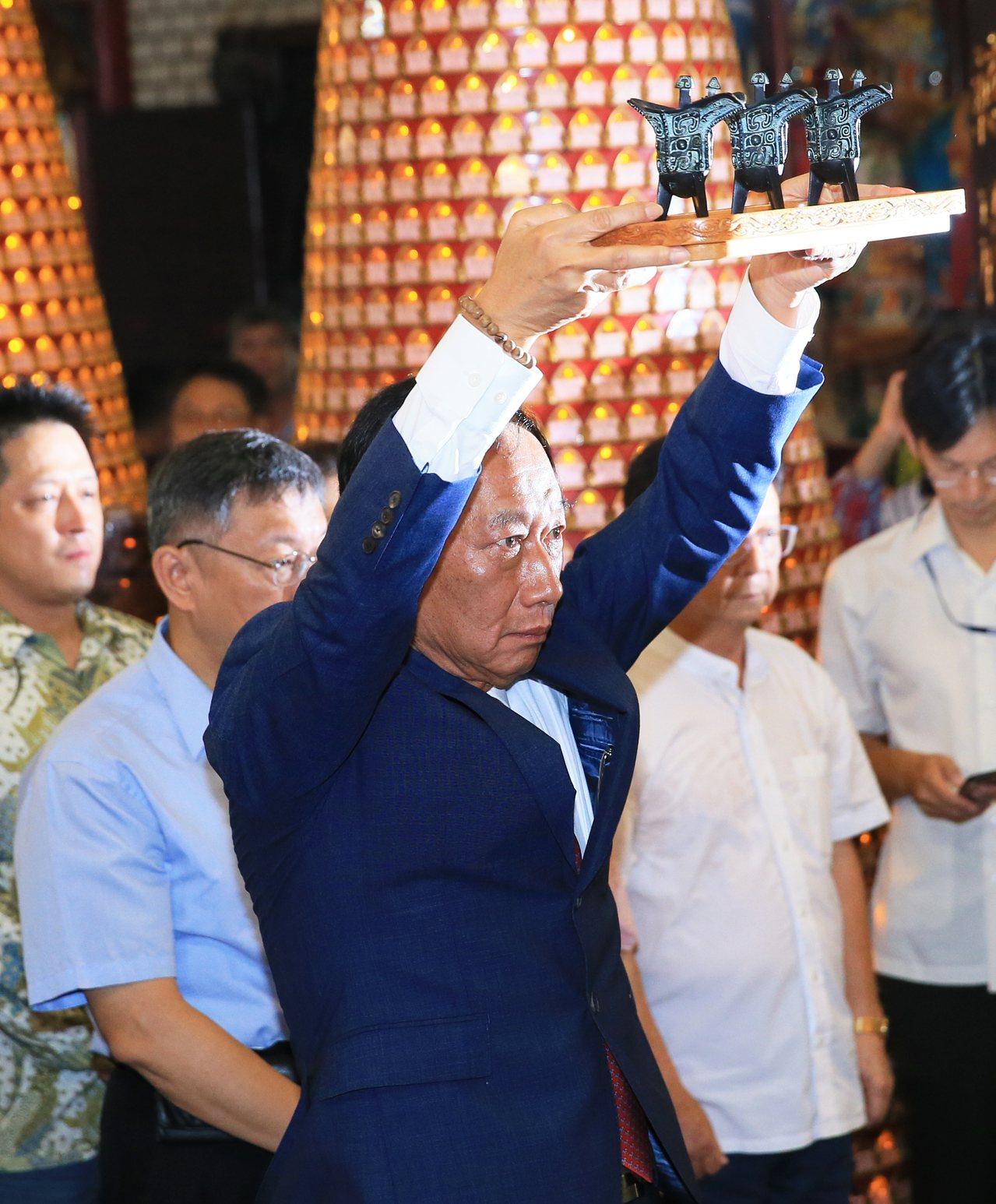 鴻海創辦人郭台銘(左二)日前與台北市長柯文哲(左)一起到新竹城隍廟參拜。本報資料...