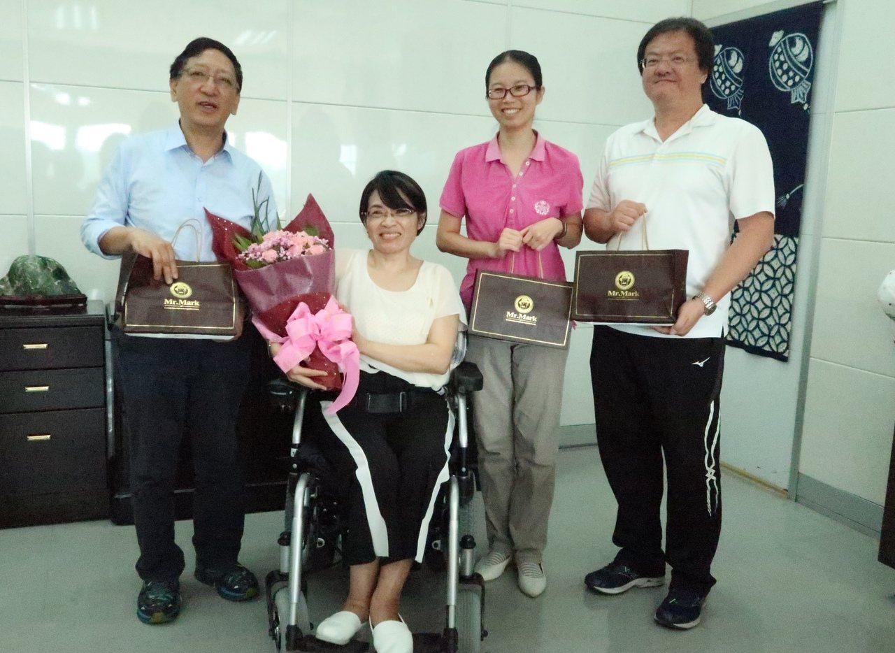 脊髓損傷者陳柳云(左二)騎著電動輪椅到教育局,感謝豪大雨當天救她脫困的教育局長吳...