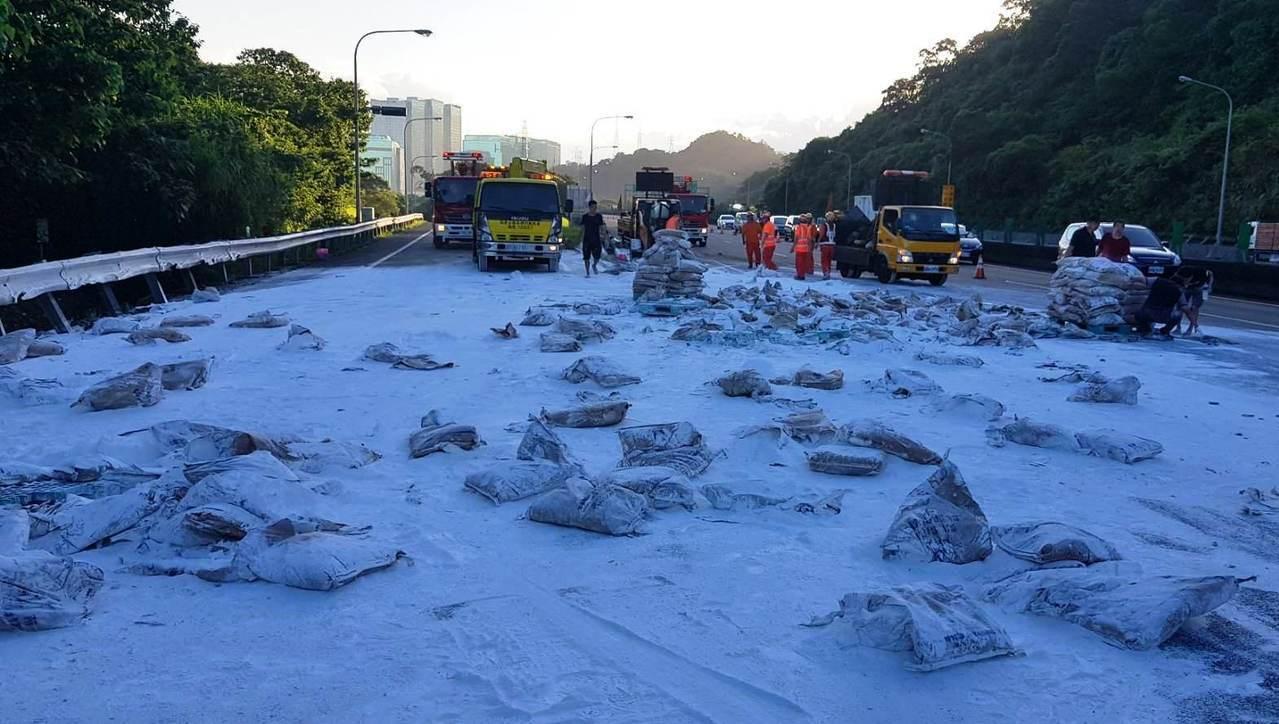 一輛載有上千包石灰粉的大貨車自撞外側路燈桿,貨物散落在車道。圖/取自國道公路警察...