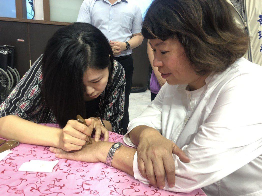 嘉市進入心理健康月,諮商心理師許家綺(左)在嘉義市長黃敏惠的手上畫「印度彩繪」。...