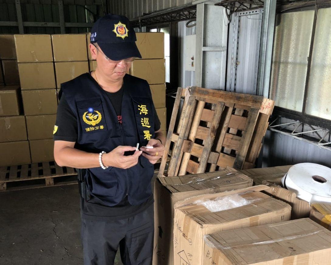 海巡人員在工廠裡細查私菸成品。記者林保光/翻攝
