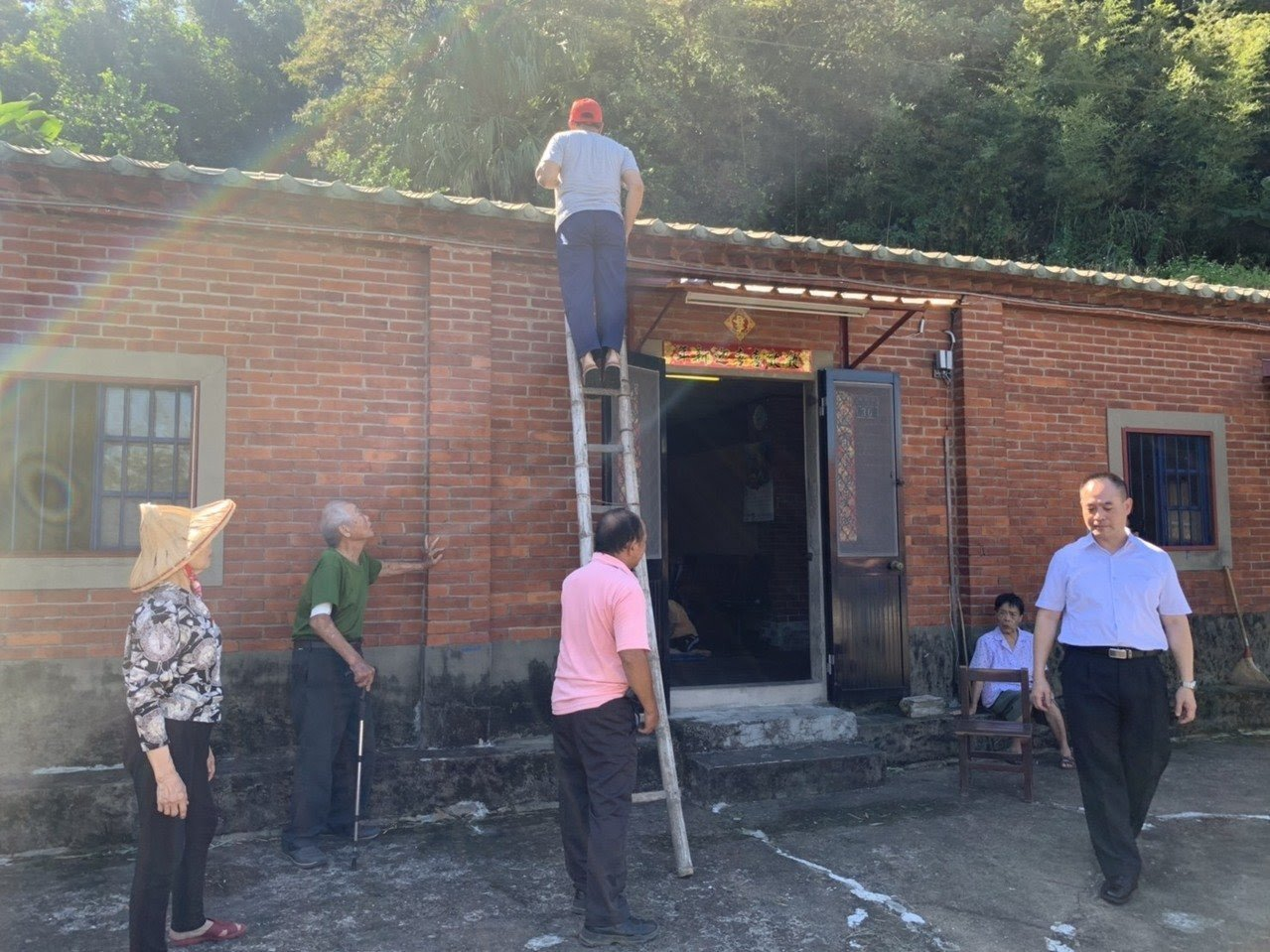 住戶架梯子爬上屋頂查看被射穿的鐵皮。記者陳斯穎/攝影