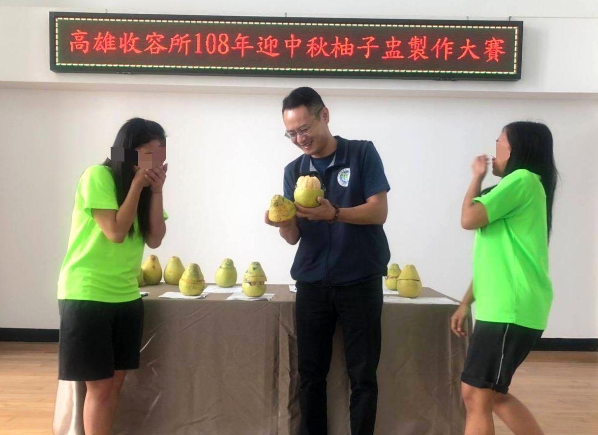 移民署高雄收容所長謝友發(中)宣布阿蘇獲柚作第一名,令阿蘇(左)喜出望外。記者林...
