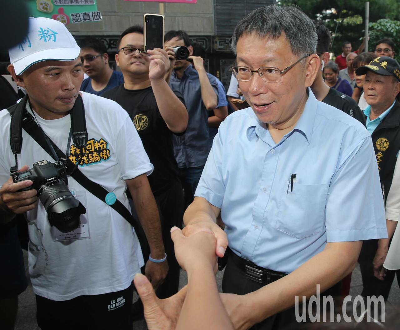 台北市長柯文哲(右)前往南投名間松柏嶺受天宮參香,與支持者一一握手致意。記者黃仲...