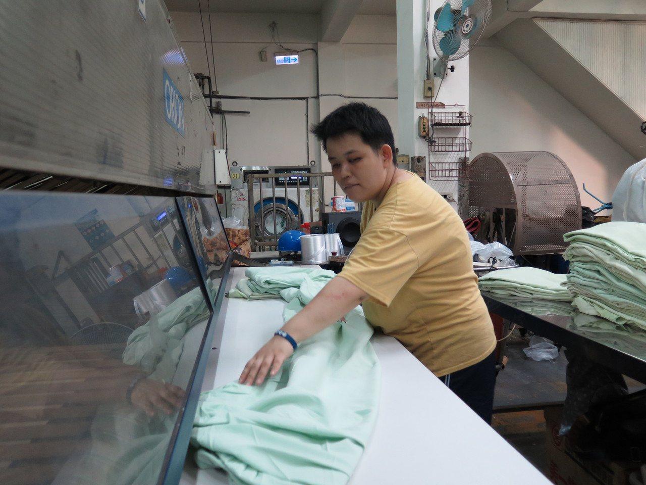 專營洗衣的晨揚國際事業長年聘用身障員工,雖然反應不比一般人快,但折疊動作仔細,一...