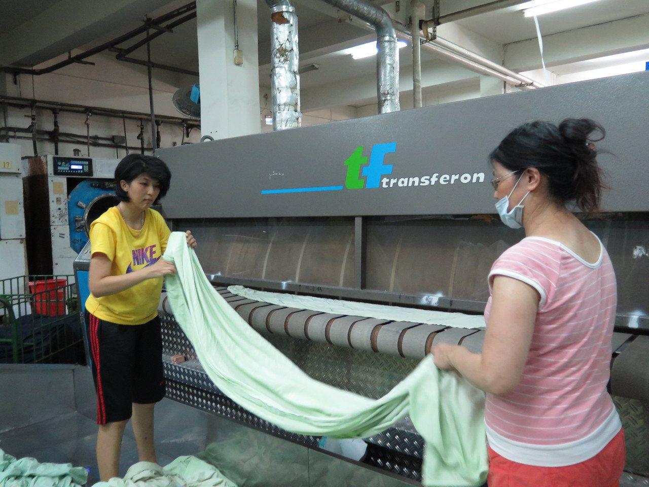 專營洗衣的晨揚國際事業長年聘用身障員工,兩人合作無間將剛洗好的被單放入滾燙機。記...