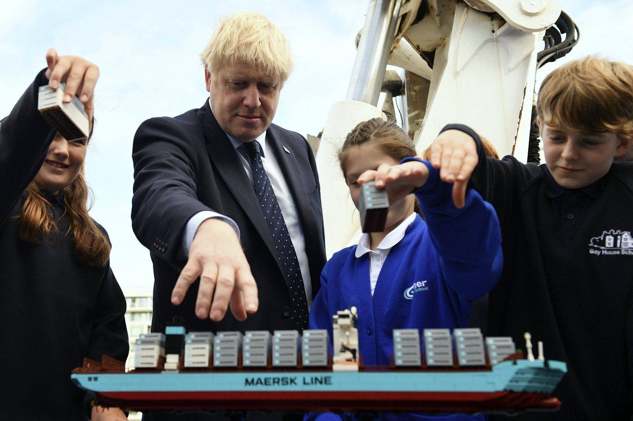 英國強生12日到泰晤士河的燈塔補給船與學童一起參加國際航運節的活動。美聯社