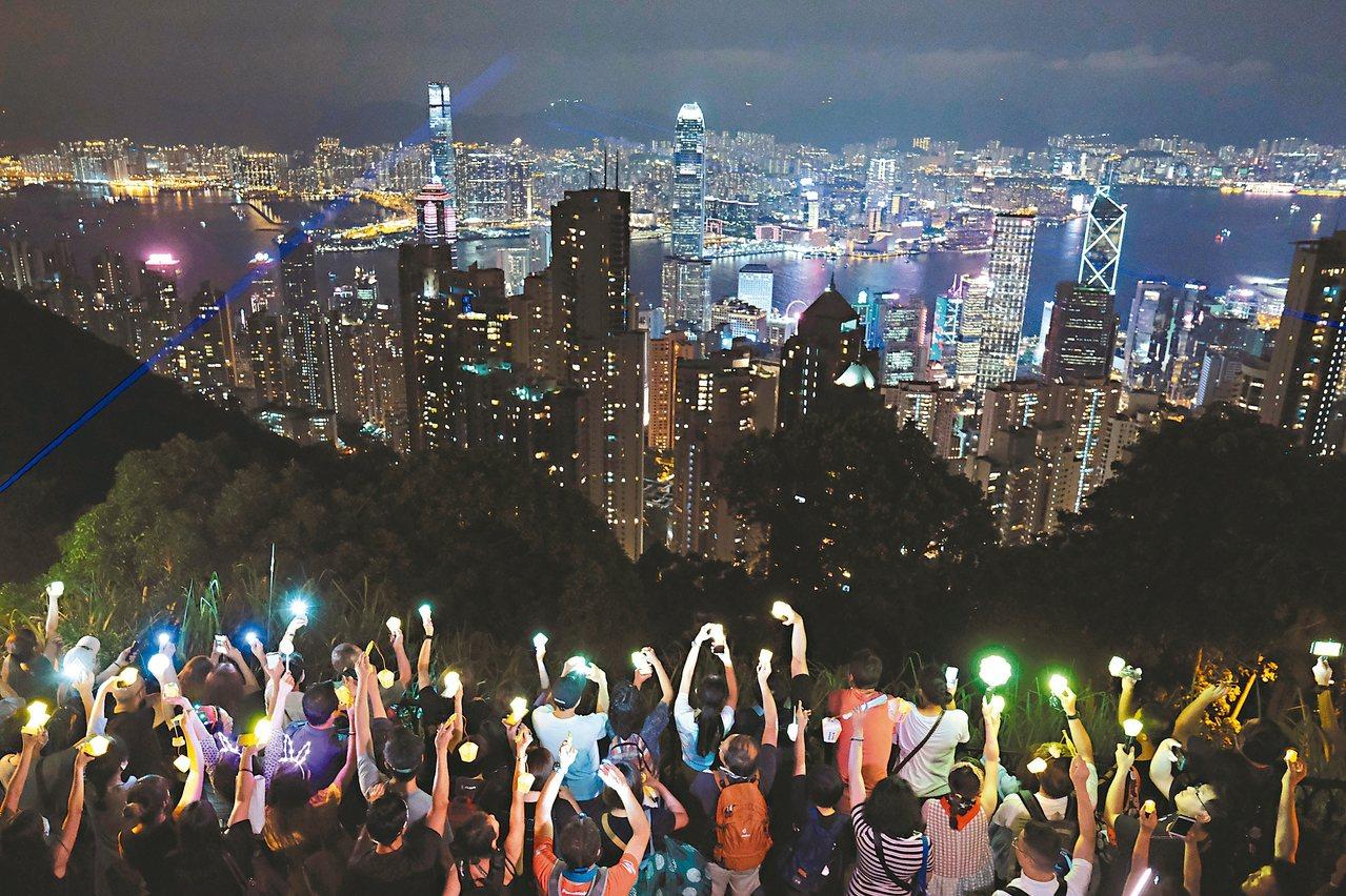 山頂舉燈 香港特別中秋夜,反送中示威者在維園賞月大合唱,也有人登上山頂高舉手機燈...