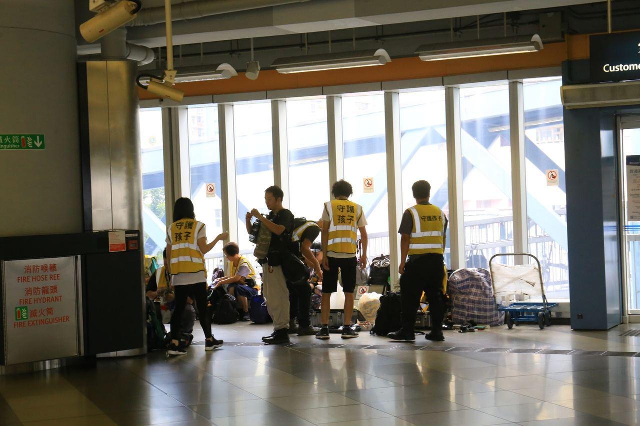 約十名身穿守護孩子黃色背心的人在天水圍站B出口外聚集。 香港01記者陳康智/...