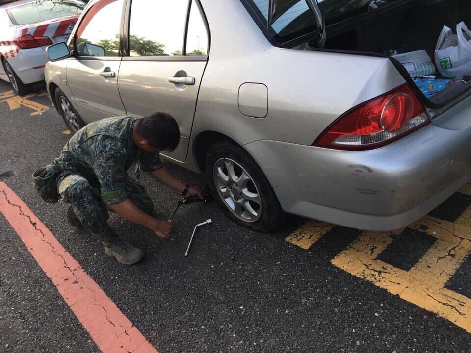陸軍八軍團裝甲564旅中士趙廷幫忙女車主換胎。圖/陸軍八軍團提供