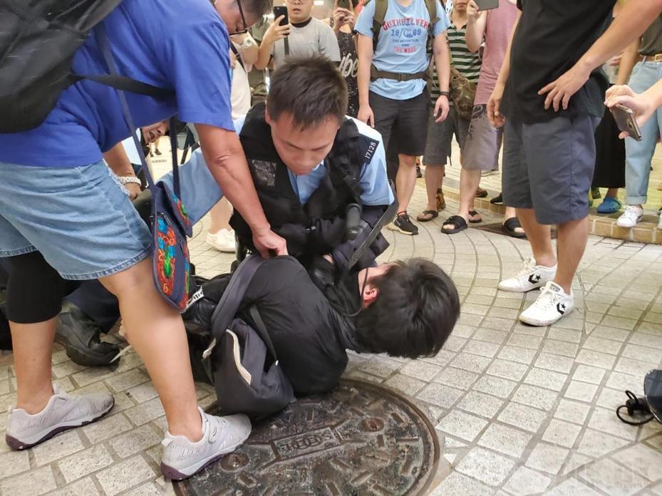 有戴口罩的黑衣人士被警方制服。圖:取自香港電台網站