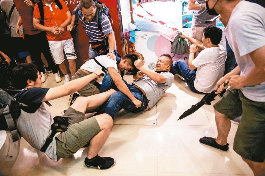 親北京民眾(右)和反送中示威者(中),昨天在九龍灣淘大商場互嗆,還大打出手 。 (法新社)