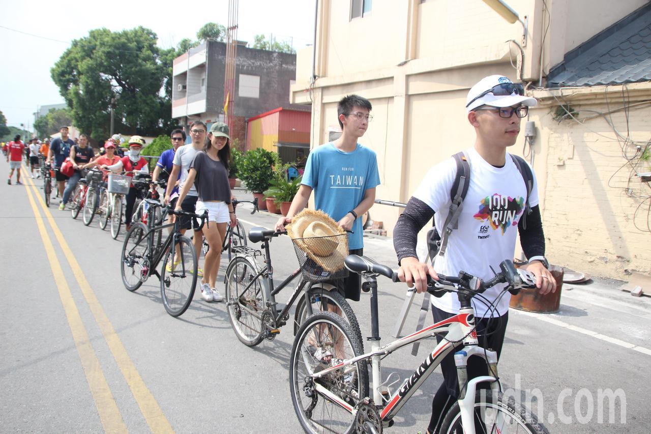 上百名自行車愛好者今天到順擇宮排隊領聯名帽。記者林敬家/攝影