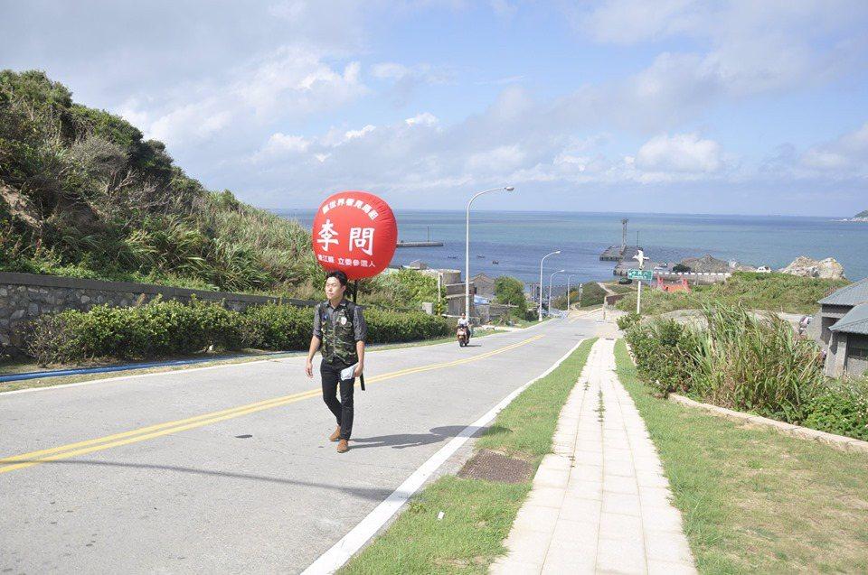 投入民進黨艱困選區的連江縣立委選舉,新人李問近日身著迷彩裝,帶著國旗和競選氣球,...