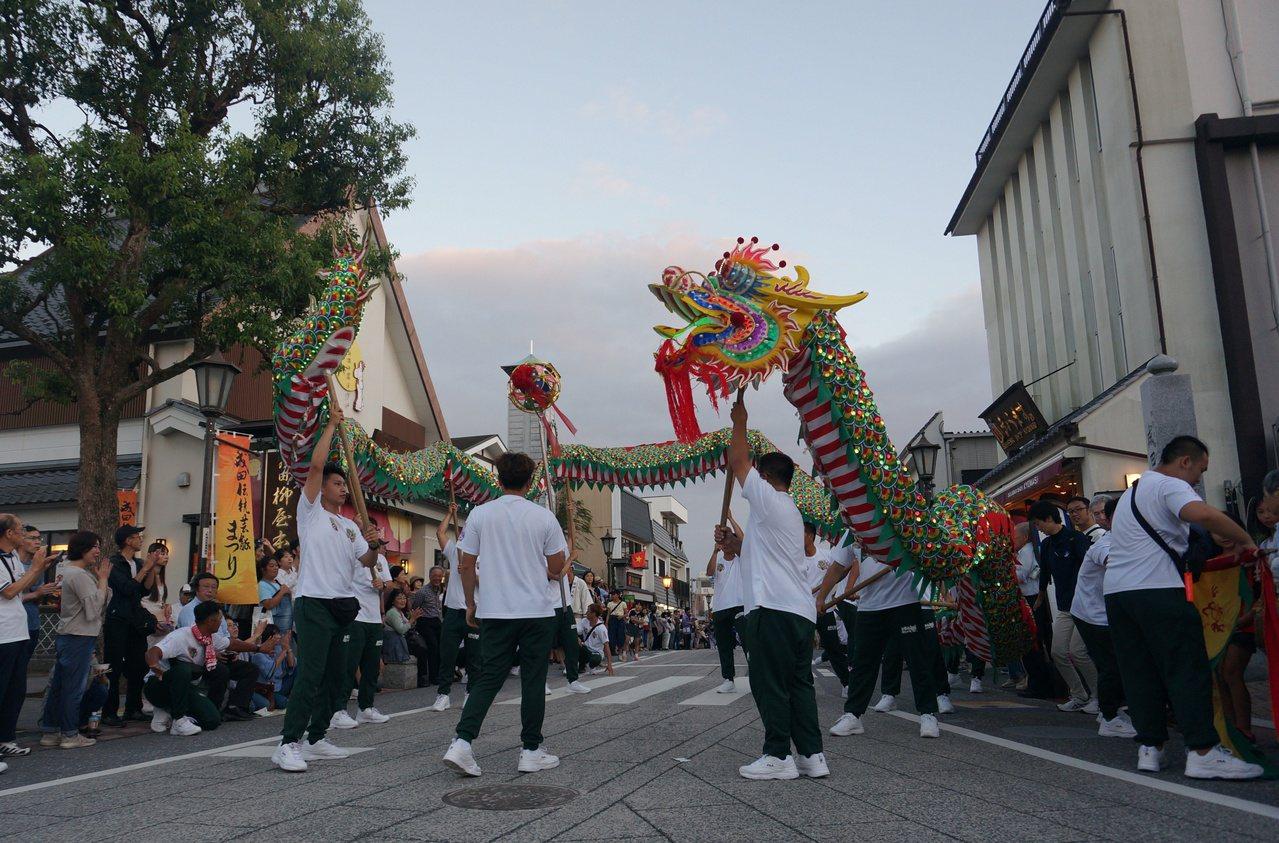 踩街遊行吸引遊客爭相與龍頭、龍珠合照,對台灣在地廟會文化很感興趣,讓日本遊客對台...