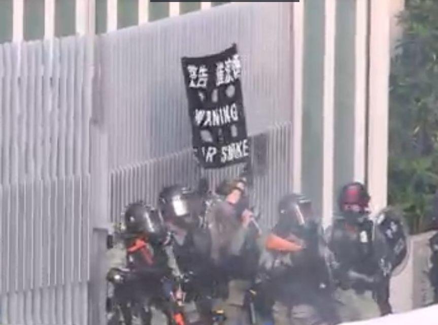 香港警方在政總舉黑旗,水馬陣起火冒煙。取自星島網