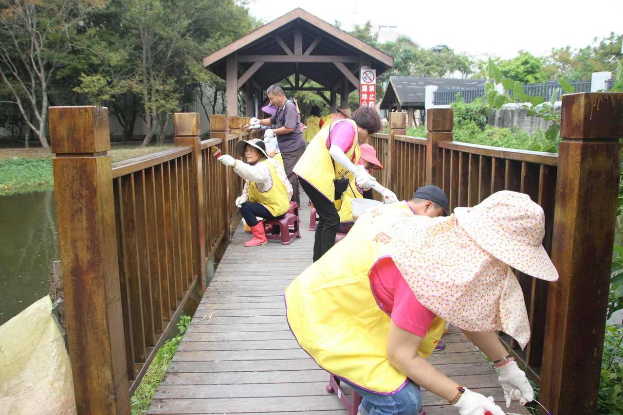 華崙社區志工今天為木棧道補漆。記者林敬家/攝影