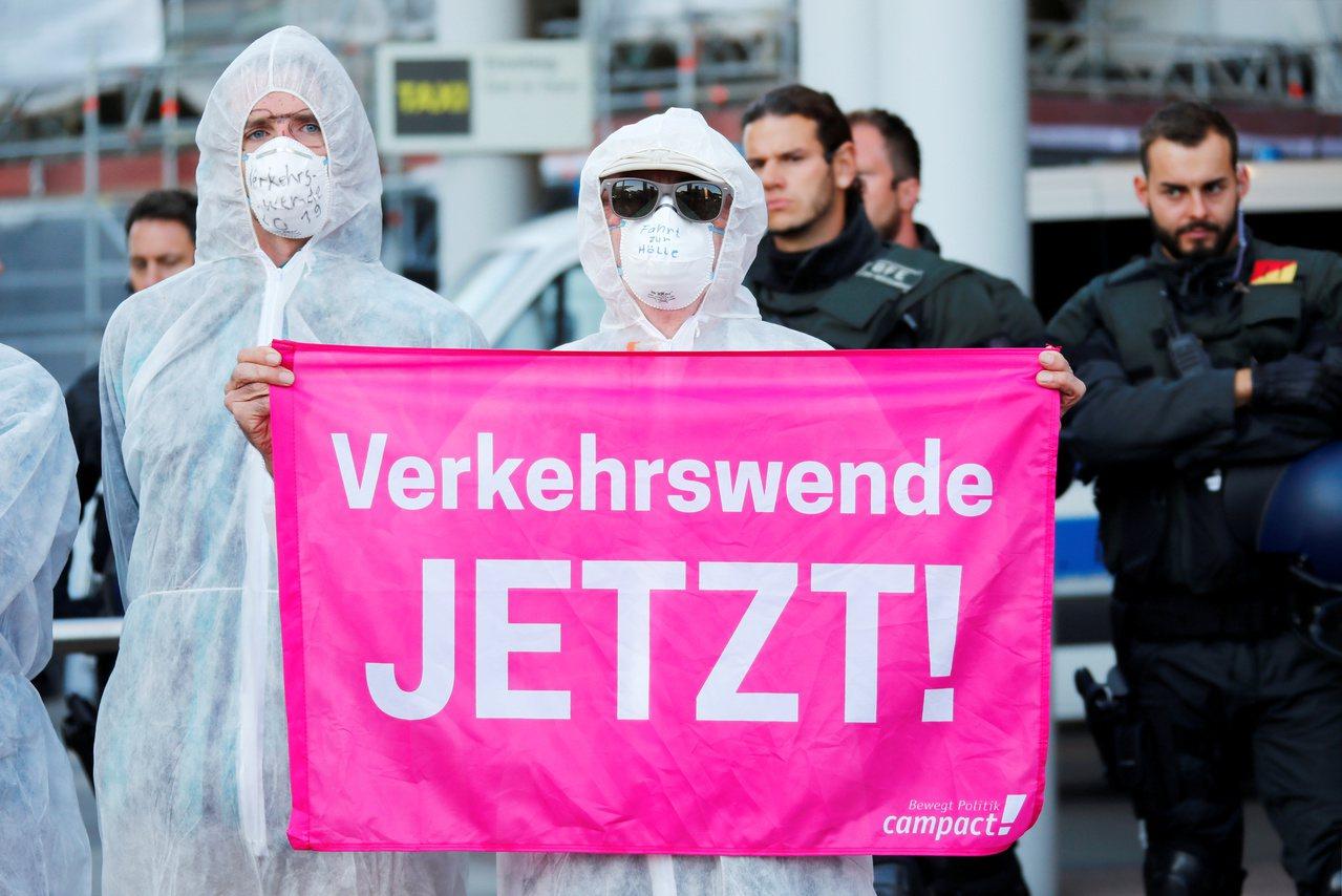 示威者15日堵住法蘭克福車展會場入口,抗議車商製造燃油車。一個蒙面抗議者拿著標語...