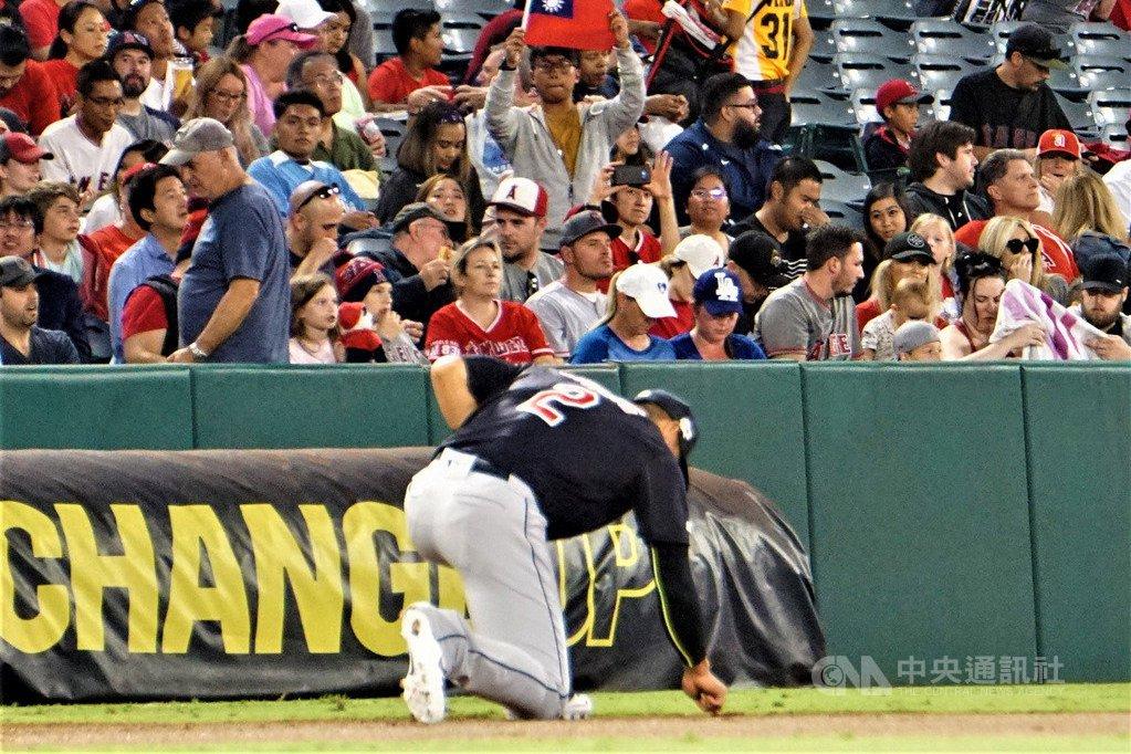 旅美棒球好手張育成(前,背號2球員)每場比賽開打前,都會在守備防區的紅土上單膝跪...