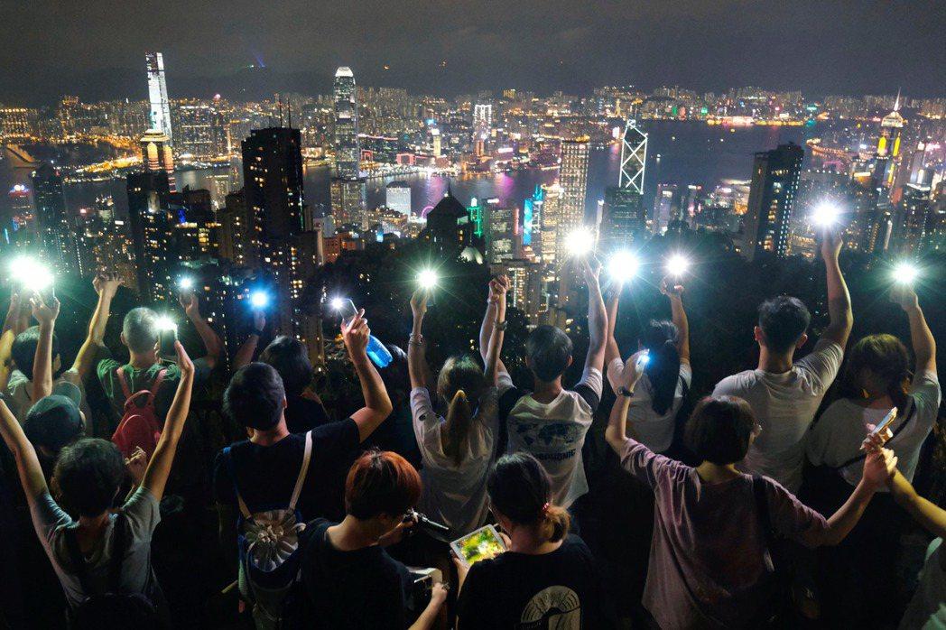 9月13日中秋節,香港市民登上山頂合唱〈願光榮〉。 圖/路透社