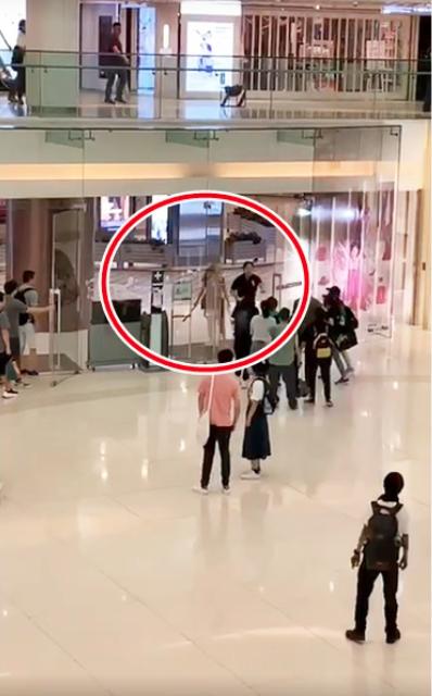 一對中年男女,疑似反對香港民眾反送中集會,兩人分別拿鐵棍和長刀到商場外揮舞。(星...