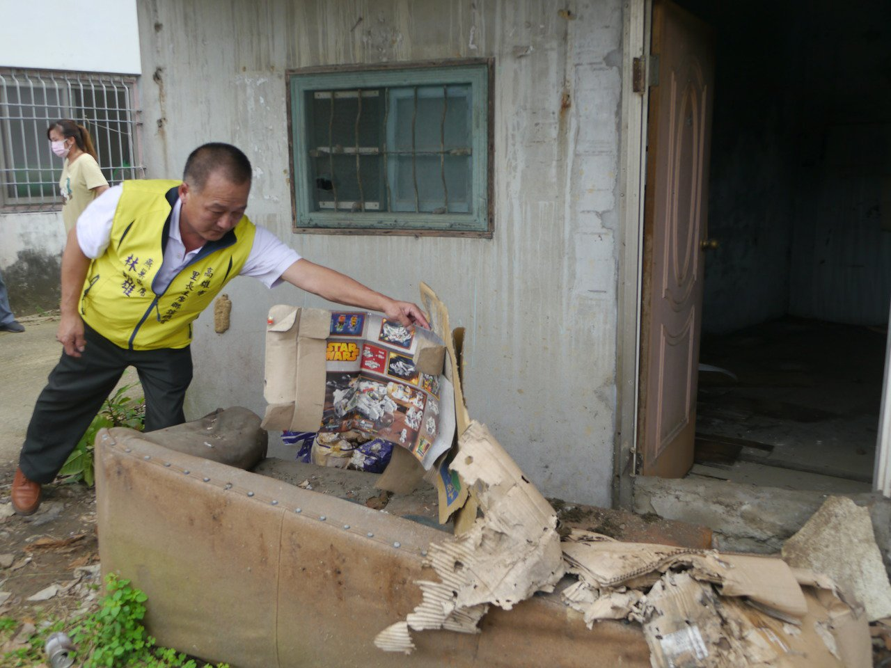 當地里長林明雄掀開廢紙,裡面就是遭人丟棄在路旁的骨灰罈。記者徐白櫻/攝影