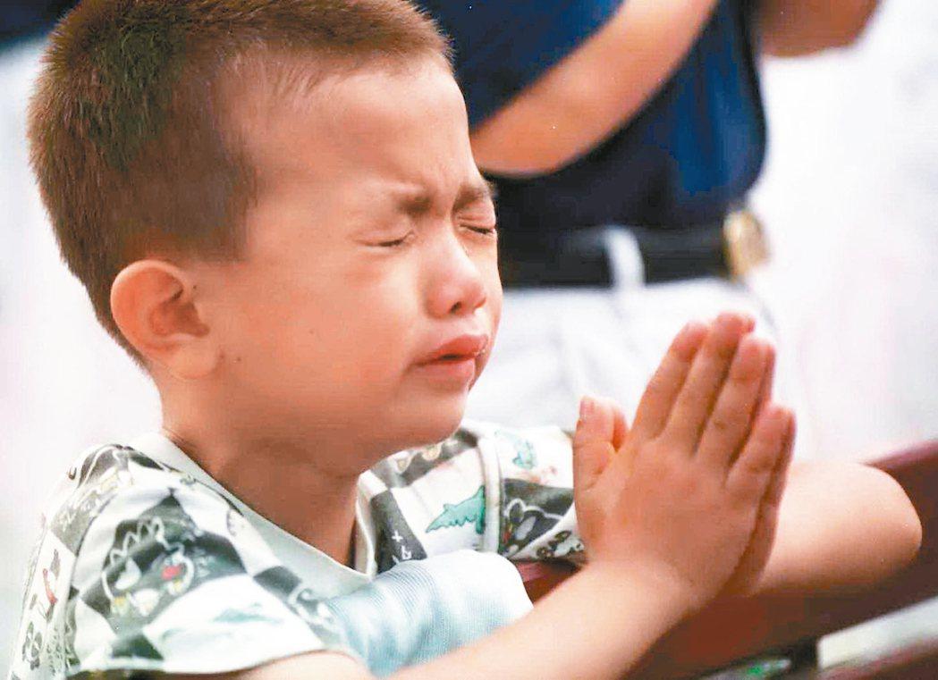 目睹震災的慘狀,南投縣中寮鄉的小男孩哭紅了眼,雙手合十為去世的人祝禱。 本報資料...
